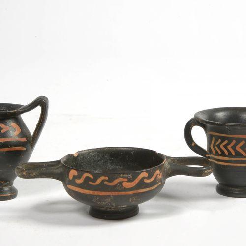 Lot de trois terres cuites miniatures vernissées noires à décor stylisé rouge or…