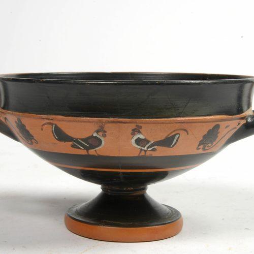 """黑釉赤土的双柄阁楼碗,脚上有砖色的楣,装饰有白色的黑色图案的公鸡。由接近画家特莱森的 """"Petits maîtres """"制作。希腊的工作。时期:公元前6世纪末。…"""