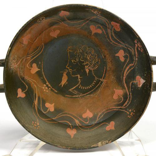 """一个黑釉陶碗或Kylix,有两个把手和橙红色的人物,中央有一个装饰有 """"带鸟的女人的轮廓 """"的徽章,周围有 """"叶子""""。芝诺集团的作品(?),意大利南部,阿普利亚…"""