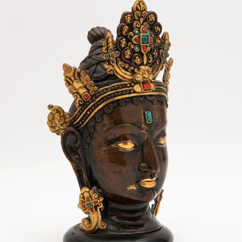 TIBET, XXème siècle Head of Buddha with bun and tiara in patinated and gilded br…