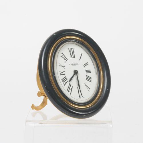 CARTIER Paris Pendulette réveil de forme ovale en métal doré, la lunette godronn…
