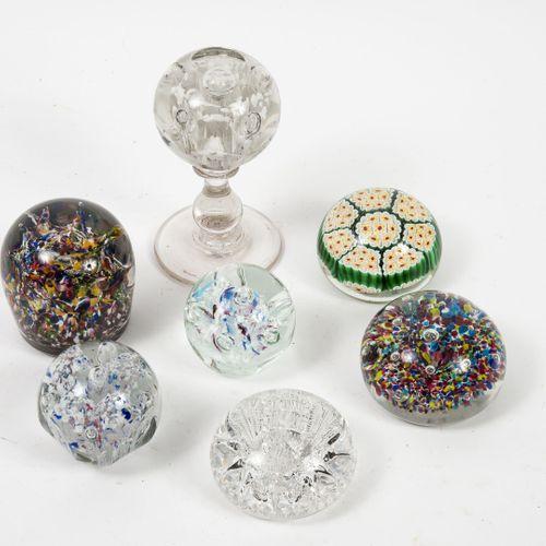 Lot de sept boules presse papier en verre, une sur piédouche.  Différents décors…