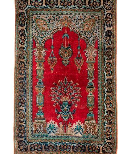 IRAN, XXème siècle Tapis en laine polychrome centré d'un mihrab à fond rouge, à …