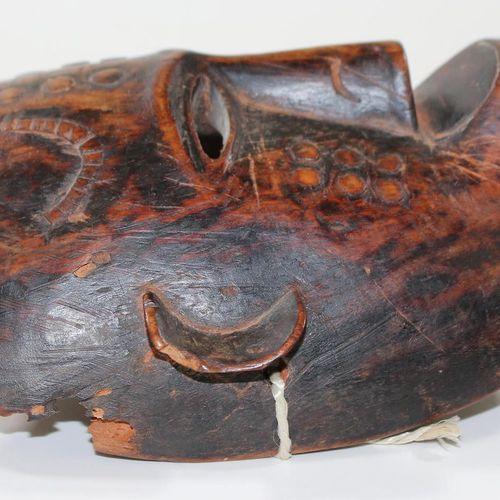 Maske der Makonde Tanzanie. Masque facial foncé avec lèvre relevée, cicatrices p…