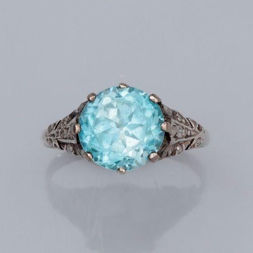 Bague en or gris 585°/°°, sertie d'un zircon bleu rond, épaulé de petits diamant…