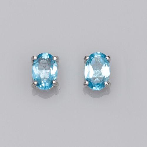 Paire de puces en or 750°/°° (18K) chacune est sertie d'une topaze bleue ovale d…