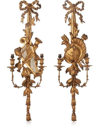Paire d'appliques en bois sculpté et doré à deux bras de lumière feuillagés. Ces…