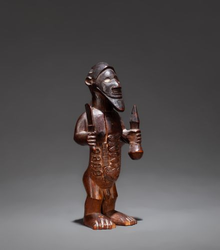 () Male statue showing a standing chief holding a receptacle in one hand and a c…
