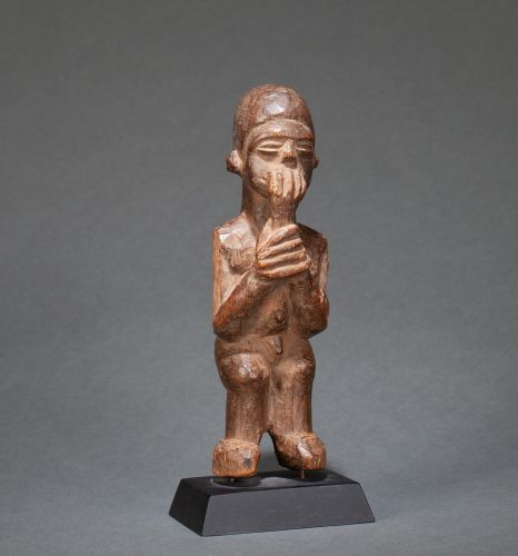 () Statuette presenting a standing naked male figure holding in his hand a prima…