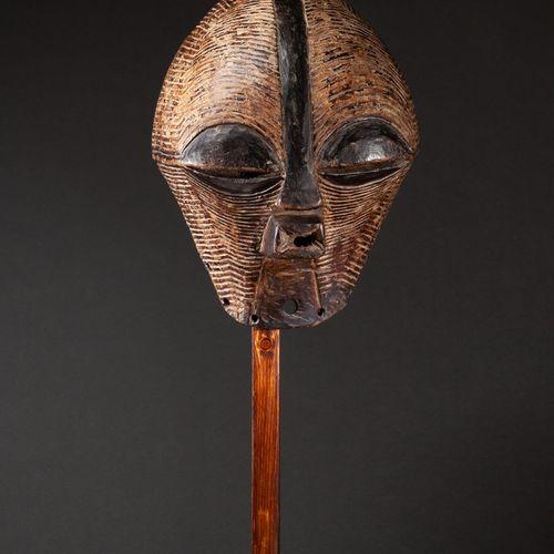 Masque Kifwébé de danse initiatique showing a face with large half closed eyes, …
