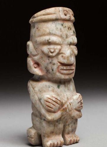 Idole anthropomorphe, elle présente une divinité assise les bras croisés sur le …