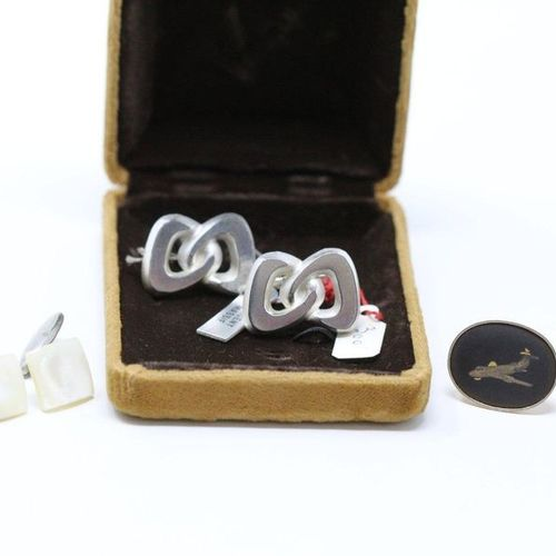 Three pairs of metal cufflinks.  One of them in a box.