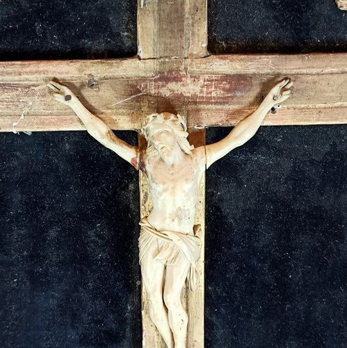 An ivory cross Christ in a gilded wood and stucco frame with stylized flower dec…