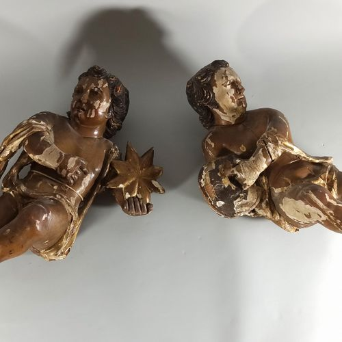 Pair of carved and polychromed wood cherubs, the bodies girded with a scarf, one…