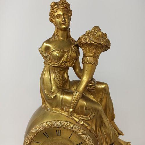 Pendule à l'Abondance  en bronze doré formée d'une haute base ornée d'un décor e…