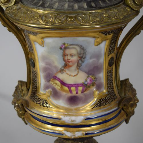 A pair of polychrome porcelain oil lamps decorated with a bust of a woman on one…