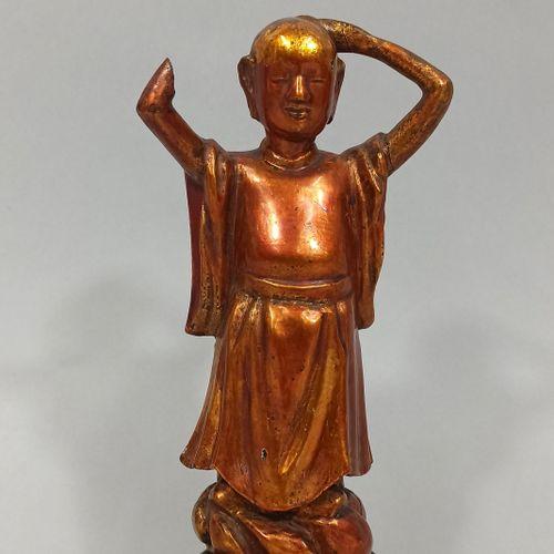 中国 约1900年  一尊金漆木雕像,年轻的佛陀正在剪发,站在一个让人联想到云的底座上。(损坏和丢失的部件)  高18厘米。  固定在一个木质底座上