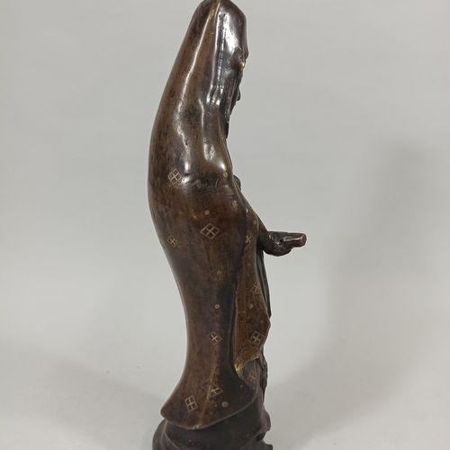 JAPON  Guanine en bronze à patine médaille tenant entre ses mains un rouleau.  H…