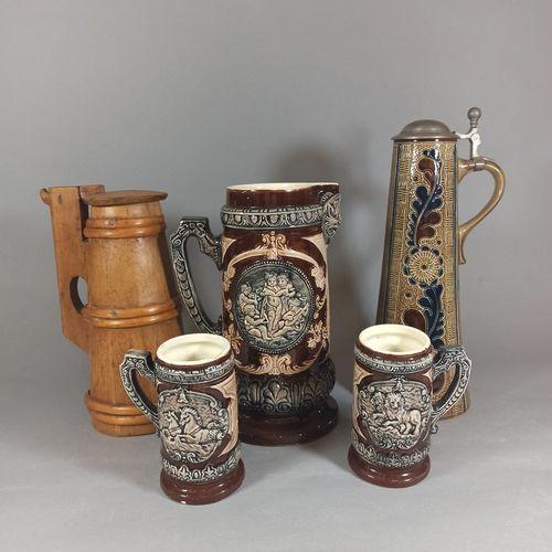一套包括一个水壶和两个杯子的瓷器,上面有神话场景的浮雕装饰。  薯片    一个木制的水壶和一个管状的带叶子装饰的搪瓷杯。