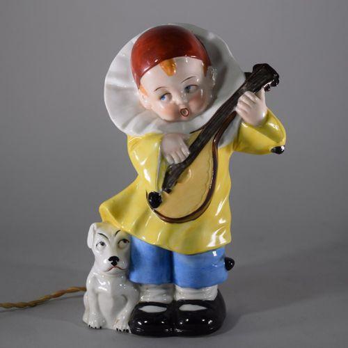 Veilleuse en porcelaine polychrome figurant un enfant déguisé en Pierrot jouant …