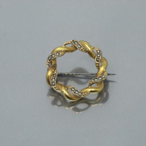 Broche en métal doré ornée de perles.