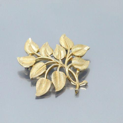 """Broche stylisant une branche feuillagée en métal doré.  Signé """"Trifari"""" à l'arri…"""