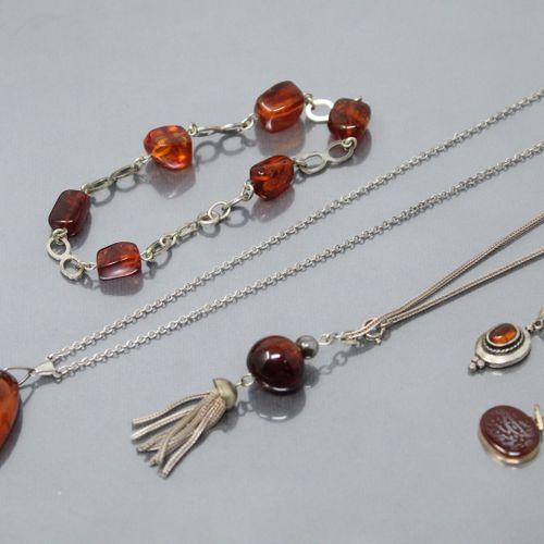 Lot de bijoux en ambre et resiné comprenant collier, bracelets et pendentifs. Le…