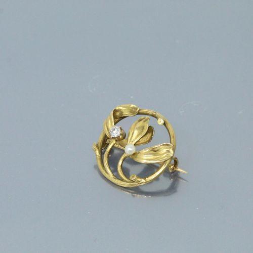 Broche ronde ajourée en or jaune 18k (750) rehaussée d'une perle et d'un diamant…