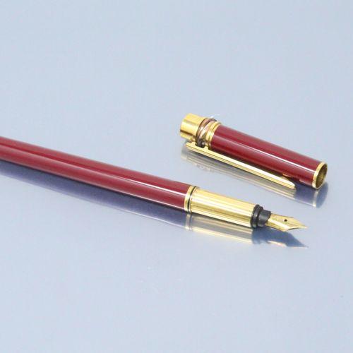 """卡地亚  红色漆面和鎏金金属钢笔。笔尖为18K(750)黄金。  由卡地亚 """"三位一体 """"模型  装在一个非传统的皮箱里。  高度:13.7厘米。13.7厘米。"""