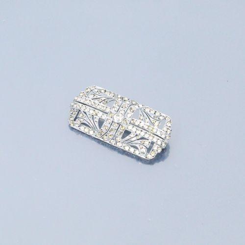 Broche en métal sous forme de plaque ornée de nombreuses pierres blanches.  Dime…