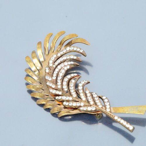 Broche en métal doré en forme de plumes ajourées, l'une d'elles pavée de pierres…