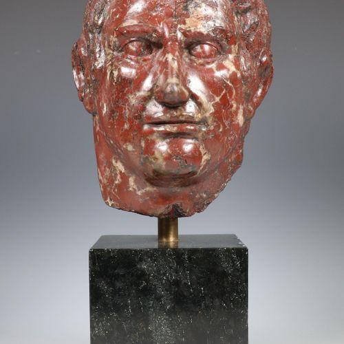 Een rood marmeren buste van een Romeinse Keizer, 20e eeuw; placed on a black har…