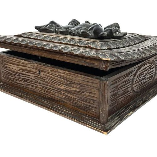 Moulded and carved oak casket with decoration on top of a stylised coat of arms.…