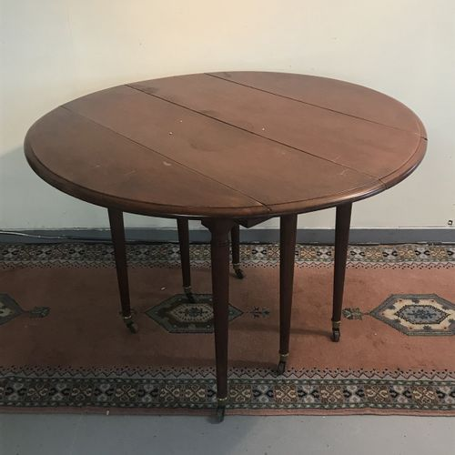 Round mahogany table, 6 legs with casters, with folding flaps  Two 49 cm extensi…