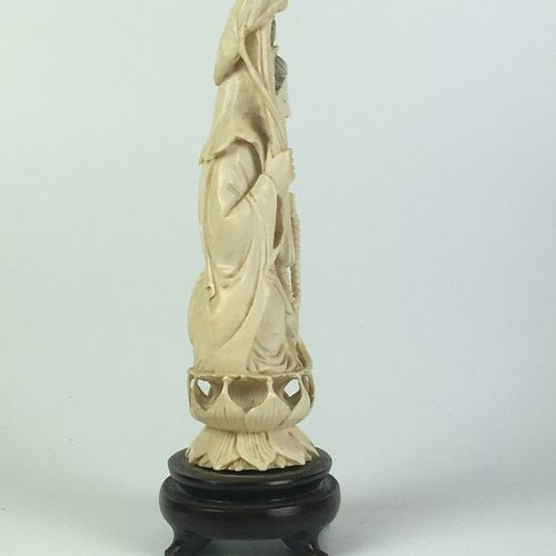CHINA Ivory statuette decorated with a deity on a lotus. Wooden base. First half…