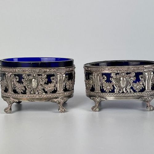 "Pair of oval saloons in chased and embossed silver with a decoration of ""Amours""…"