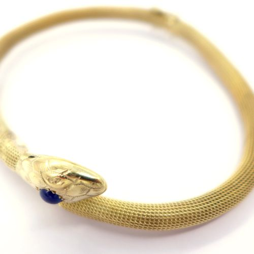 BRACELET in 14K yellow gold representing a coiled snake holding a cabochon sapph…