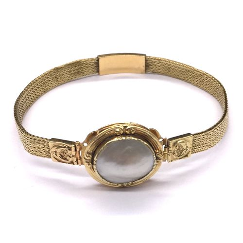 BRACELET holding an oval white pearl encircled by a yellow gold frame with an ar…
