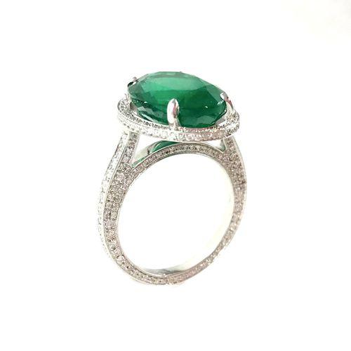 IMPORTANT RING holding a 6.40 carat oval emerald in a brilliant cut diamond sett…