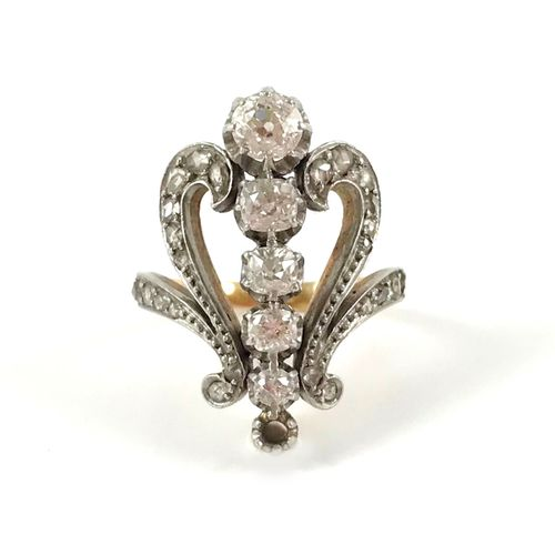 1900's ring holding a design of scrolling rose cut diamonds around a line of old…