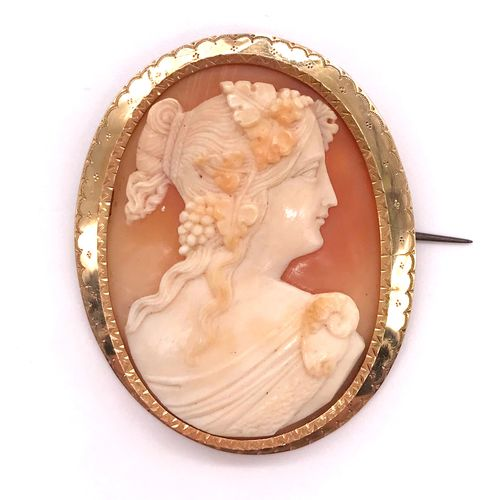 A cameo of a woman in profile in an 18K yellow gold frame with finely chased dec…
