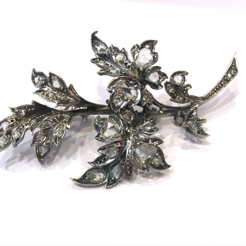 TREMBLING BROOCH WITH TRANSFORMATION holding a flower design on a leafy branch s…