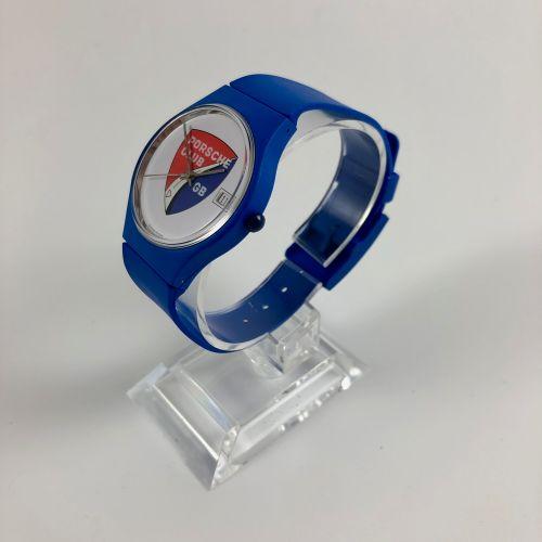 PORSCHE CLUB GB. Montre en plastique bleu, boitier rond. Cadran représentant le …