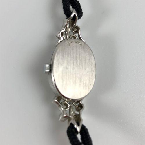 QUARTZ OR. Réf 21566. Montre de femme en or gris 585/1000. Boitier ovale cerclé …