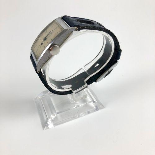 """LIP T18。编号 : 25813。 不锈钢腕表,""""坦克 """"表壳,签名的白色表盘,阿拉伯数字和巴顿数字。6点钟方向的秒针计数器。手动上链机械机芯。黑色皮革拉力…"""