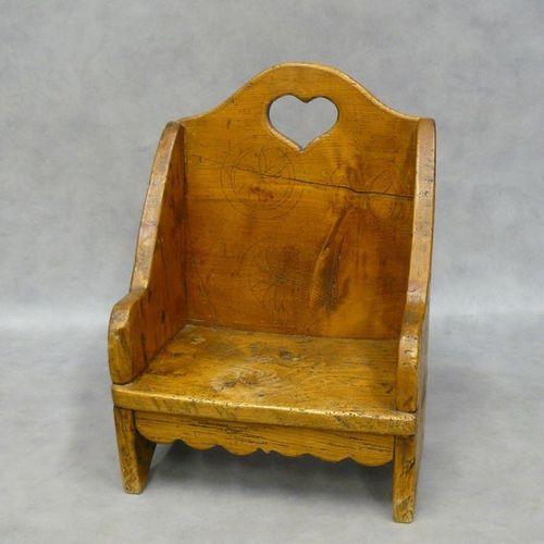 Un fauteuil d'enfant en bois, le dossier ajouré d'un cœur et orné de trois rosac…