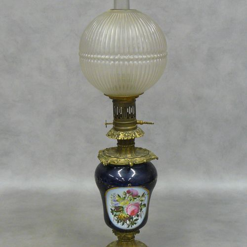 Une lampe à pétrole en porcelaine (électrifiée) à décor floral polychrome sur fo…