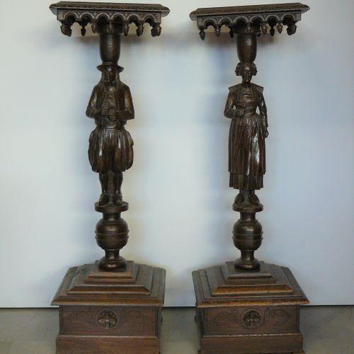 Deux sellettes formant pendant en chêne sculpté représentant un couple de Breton…