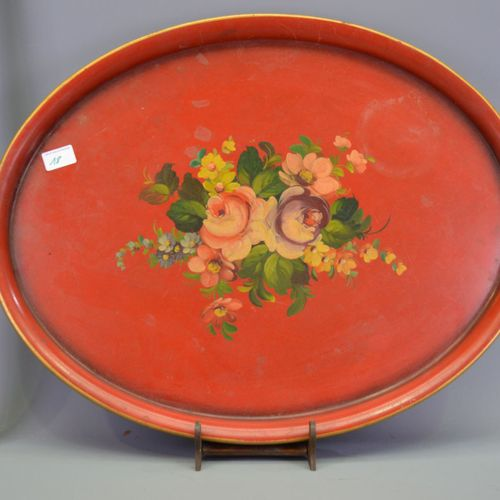 Tray in painted sheet metal with flower decoration on a red background.