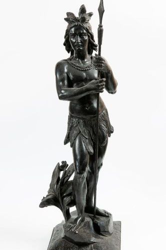 Blackened wooden sculpture representing an Indian warrior with feet holding a sp…